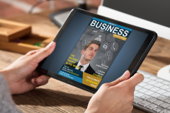 Businessperson Looking At Business Magazine On Digital Tablet At Office Desk